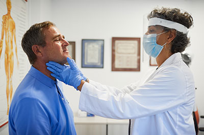 doctor checking patient thyroid